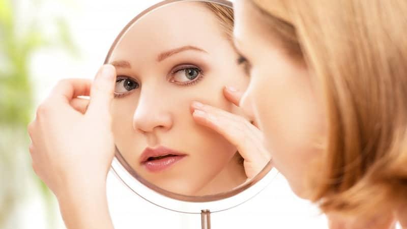 Ciri CIri Cream Pemutih Wajah Berbahaya - Perempuan Mengecek Wajah di Cermin